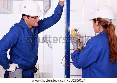 Male electrician supervising female apprentice - stock photo
