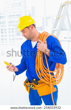 Male electrician with wire roll looking at reading multimeter in bright office - stock photo