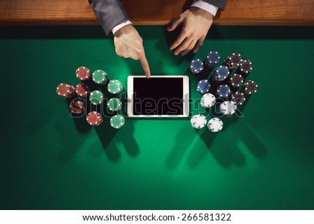Male elegant player touching a digital tablet screen with chips all around on green table, top view - stock photo