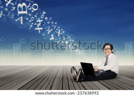 Male elementary school student sitting outdoors while using laptop computer to send information - stock photo