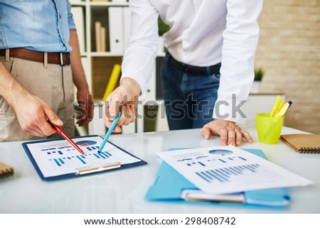 Male employees discussing business document in office - stock photo