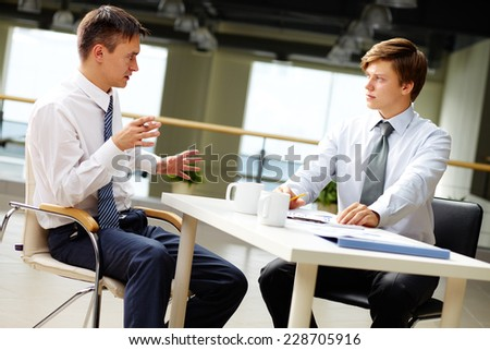 Male employees sharing and discussing their ideas or business plans