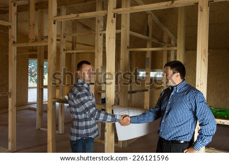Male Engineer and Architect Showing Handshake at Building Site, Emphasizing Both Agreed to Project Design. - stock photo