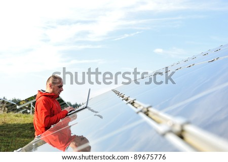 Male engineer at work place, solar panels in background - stock photo