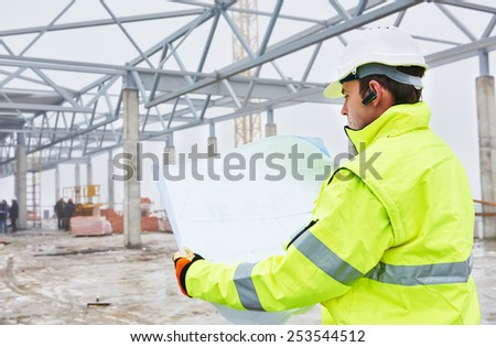 male engineer construction foreman manager outdoors indoors at building site with blueprints - stock photo