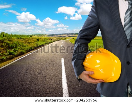 Male engineer on rural road through agricultural meadow. Business man holding yellow hardhat for safety of the workers on sunny landscape background.  - stock photo