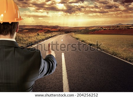 Male engineer on straight asphalt road showing thumb up as sign of success.  - stock photo