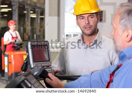 male engineer talking to forklift operator in warehouse - stock photo