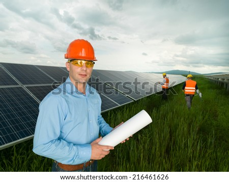 male engineer wearing protection equipment, standing in solar panel station, holding blueprints, with two other workers in background - stock photo