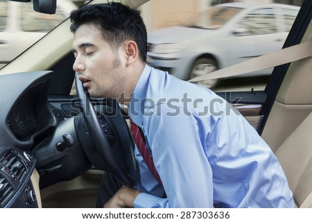 Male entrepreneur sleeping in the car while driving on the road at traffic jam - stock photo