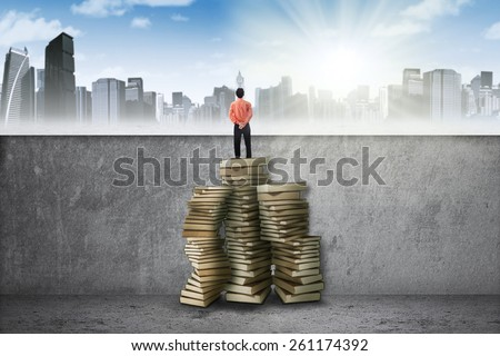 Male entrepreneur standing on a pile of books to past the obstacle and look at the city - stock photo