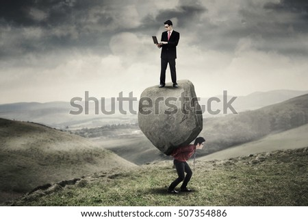 Male entrepreneur standing on the rock and using laptop computer while his partner lifting the rock on the hill