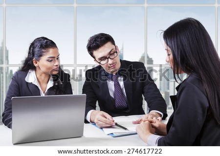 Male entrepreneur with his assistant showing a business document to his colleague - stock photo