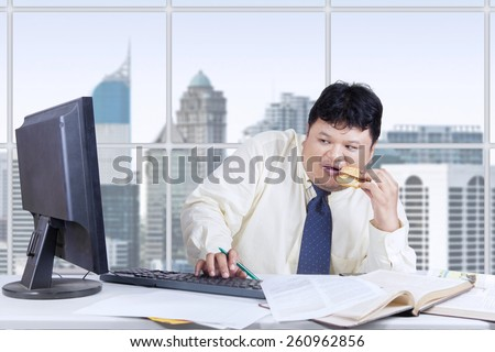 Male entrepreneur working in the office while eating burger and looks fear when looking at computer monitor - stock photo