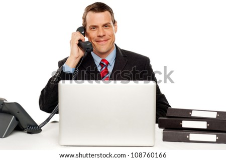 Male executive communicating with client on telephone and feeding instruction on laptop - stock photo