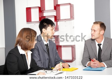 Male executive discussing with his colleagues during a meeting - stock photo