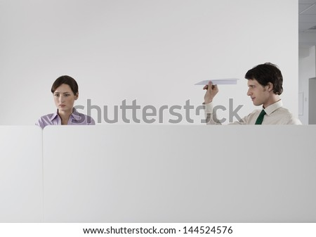 Male executive throwing a paper aeroplane at female colleague in the office - stock photo