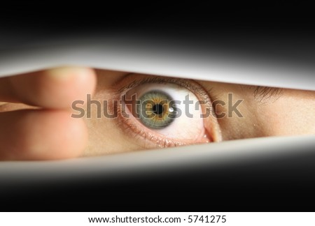 Male eye peering into envelope/package or peering through blinds - stock photo