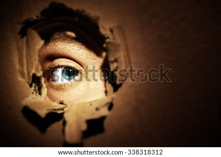 Male eyes spying through a hole in the wall - stock photo