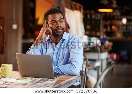 Male Fashion Designer Working At Laptop In Studio - stock photo