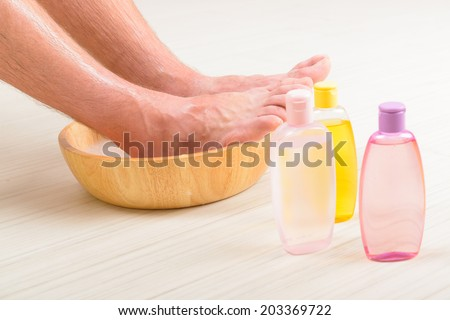 Male feet in a bowl with water and soap, cosmetics in bottles, hygiene and spa concept - stock photo