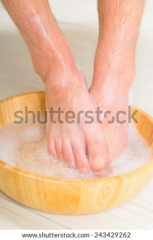 Male feet in a bowl with water and soap, hygiene and spa concept - stock photo
