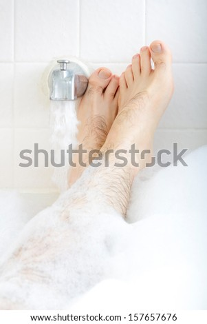Male feet soaking in the bathtub with faucet running water. - stock photo