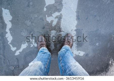 Male feet standing on frozen puddle with thin ice and falling leaves - stock photo