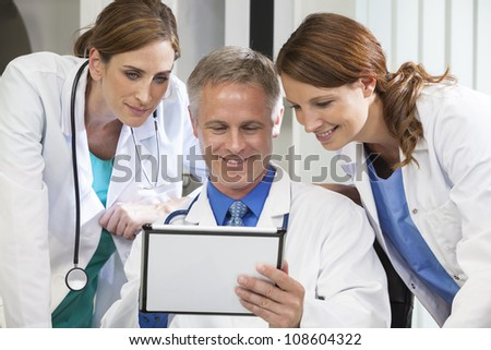 Male & female medical doctors medical team using tablet computer in a hospital office - stock photo