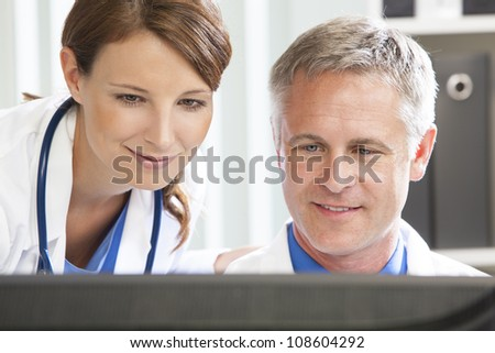 Male & female medical doctors using computer in a hospital office - stock photo