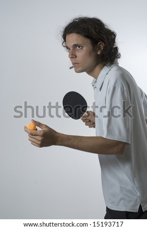 Male figure serving a ping-pong ball.  He has a racket and a ping-pong ball in his hand. His expression is intense. Vertically framed shot. - stock photo