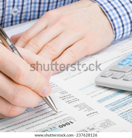 Male filling out 1040 United States of America Tax Form - taxing concept - stock photo