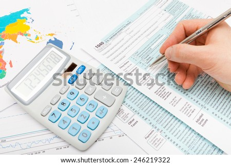 Male filling out US 1040 Tax Form - stock photo