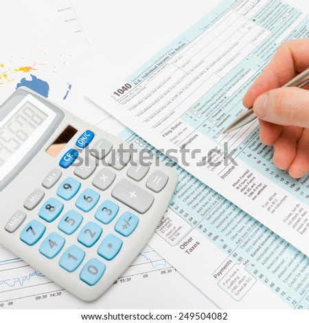 Male filling out US 1040 Tax Form - studio shot - stock photo