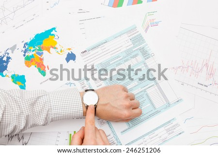 Male filling out 1040 US Tax Form - tax time - stock photo