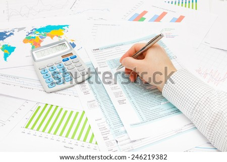 Male filling out 1040 US Tax Form with ball pen - stock photo