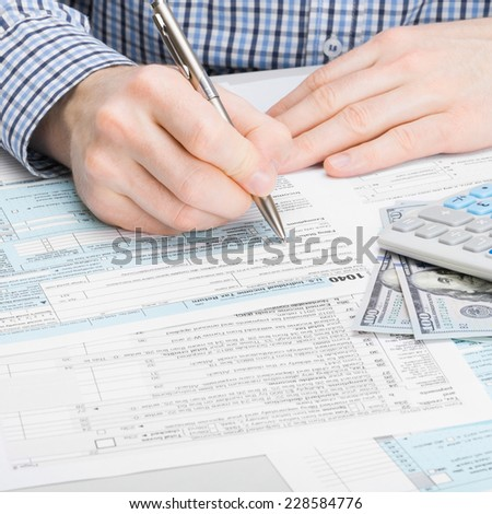 Male filling out 1040 USA Tax Form - stock photo