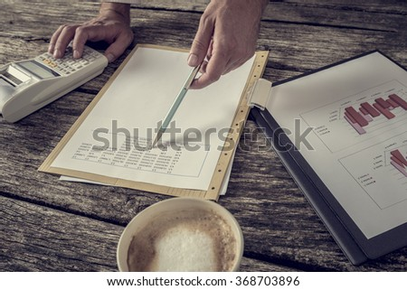 Male financial adviser pointing with pen to statistical data numbers as he calculates and checks annual report presented in graphs and charts. - stock photo