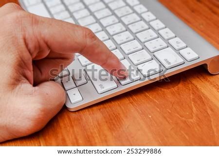 Male finger press enter on white keyboard. - stock photo