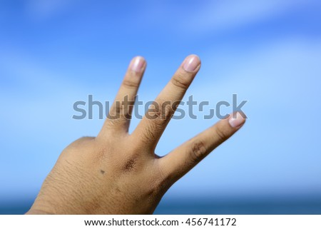 Male fingers showing number 3 isolated on bokeh blue-sea background. Copyspace is available. - stock photo