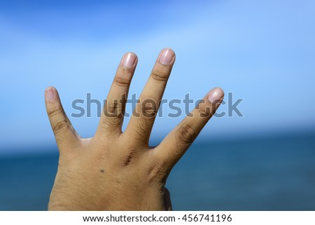 Male fingers showing number 4 isolated on bokeh blue-sea background. Copyspace is available. - stock photo