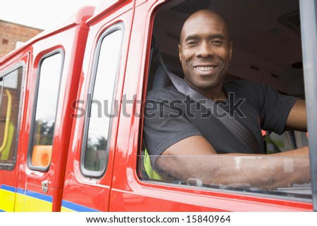 Male firefighter sitting in the cab of a fire engine