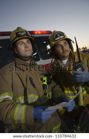 Male firefighters in safety uniform looking away - stock photo