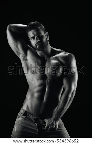 Male fitness model Konstantin Kamynin posing shirtless on black background