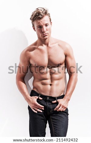 Male fitness model wearing blue jeans. Blonde hair. Against white wall. - stock photo
