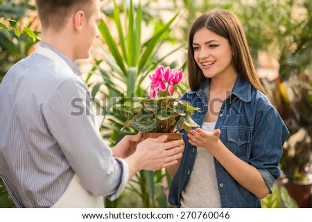 Male florist giving young female flower pot.