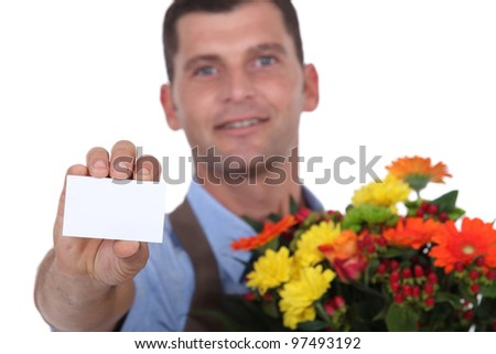 Male florist holding a blank business card - stock photo