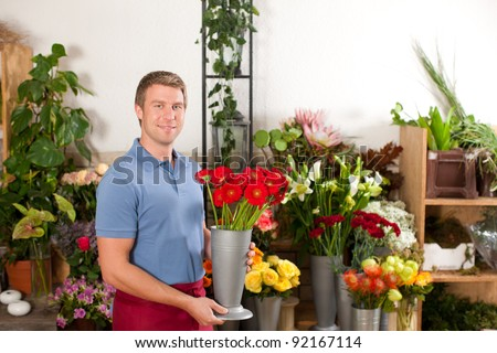 Male Florist in flower shop or nursery presenting his plants on display