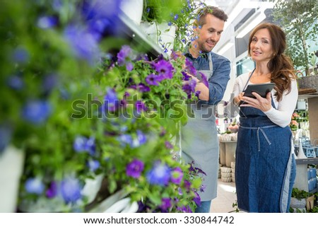 Male florist looking at female colleague using digital tablet in flower store - stock photo