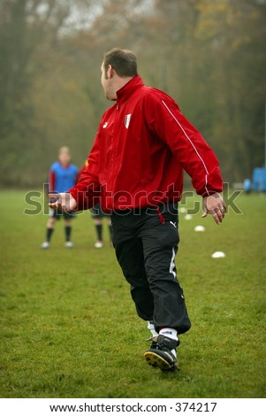 male football coach in red top and black tracksuit bottoms - stock photo